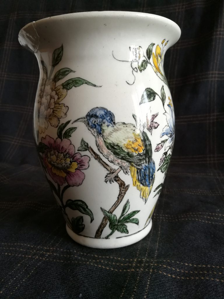 Un vaso in terracotta bianca con decorazioni vegetali e un volatile su un ramo, visto di lato
