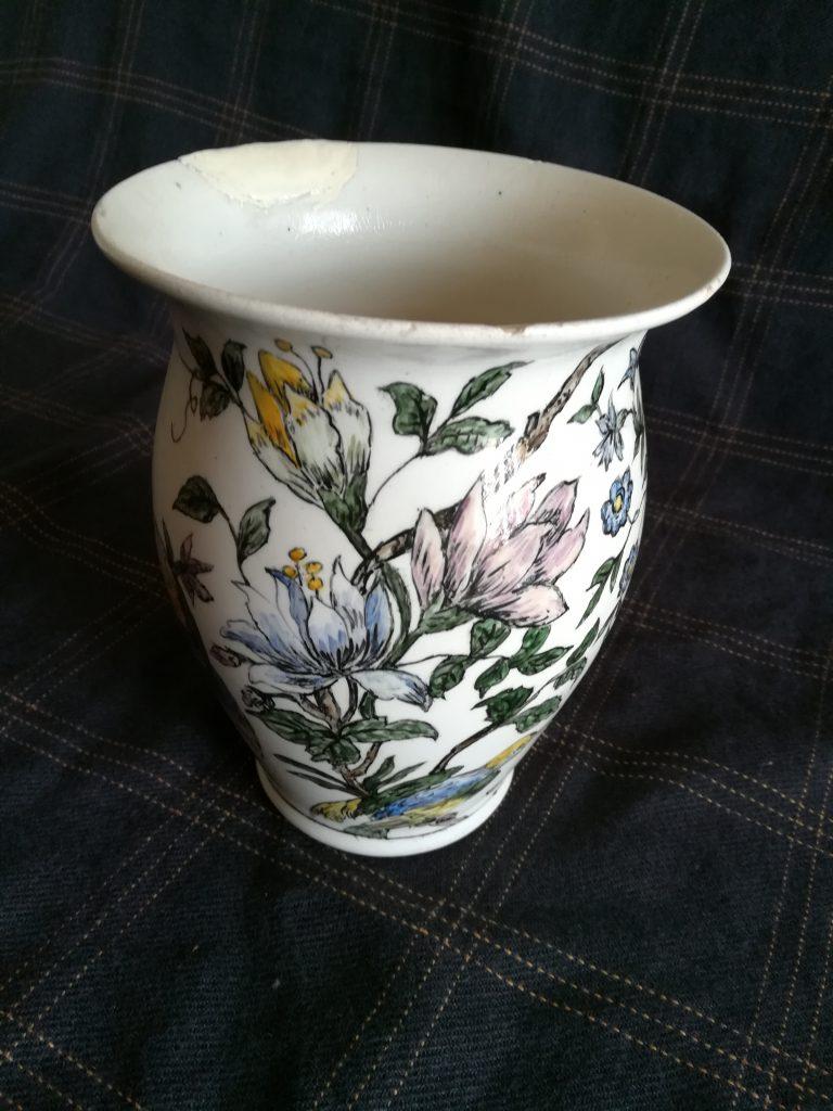 Un vaso in terracotta bianca con decorazioni vegetali e fiori, visto di lato
