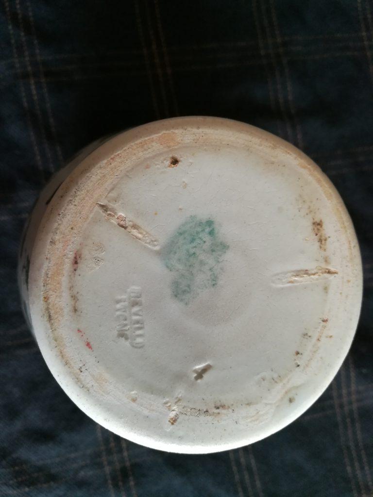 Un vaso in terracotta bianca visto dal basso, con il marchio di fabbricazione della ditta Revelli