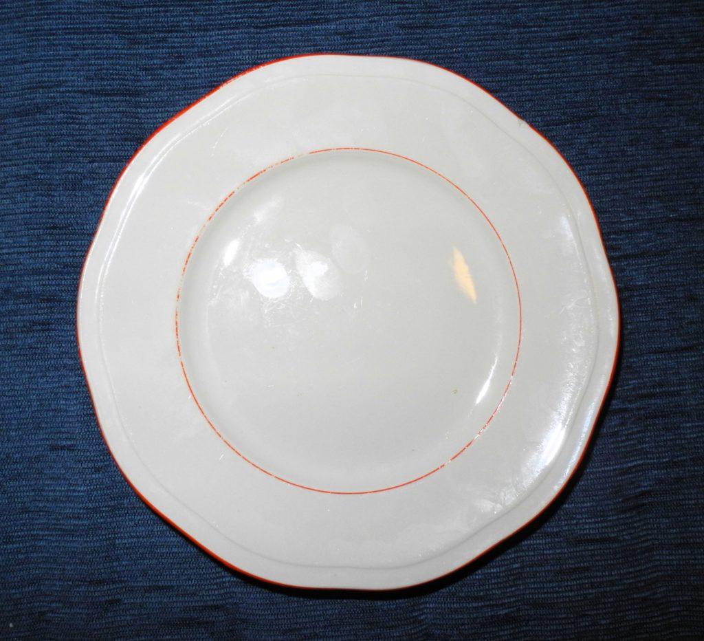 Piatto in terraglia bianco con sottili bordi arancioni, in parte consumati